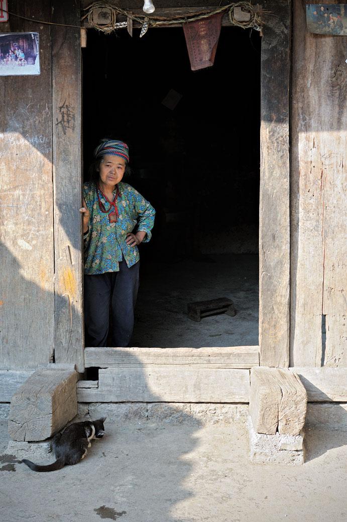 Femme Hmong à la porte d'une maison traditionnelle, Vietnam