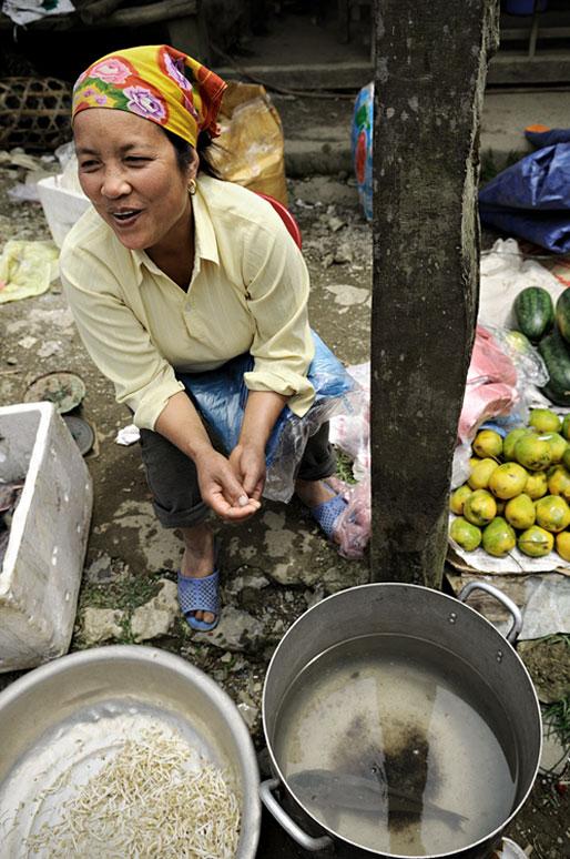 Femme assise qui rigole au marché de Quyet Tien, Vietnam