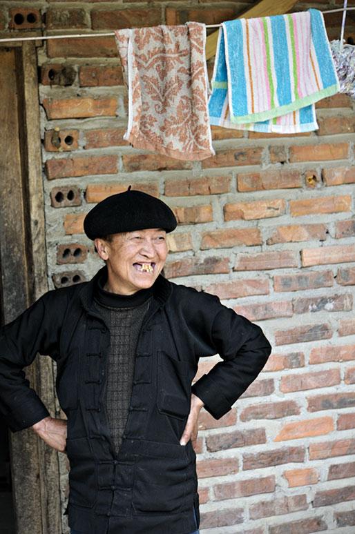Femme au sourire édenté devant sa maison, Vietnam