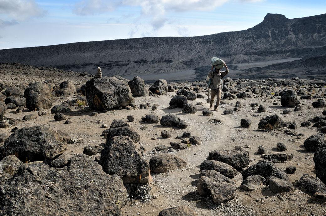 Porteur et pierres volcaniques sur le Kilimandjaro, Tanzanie