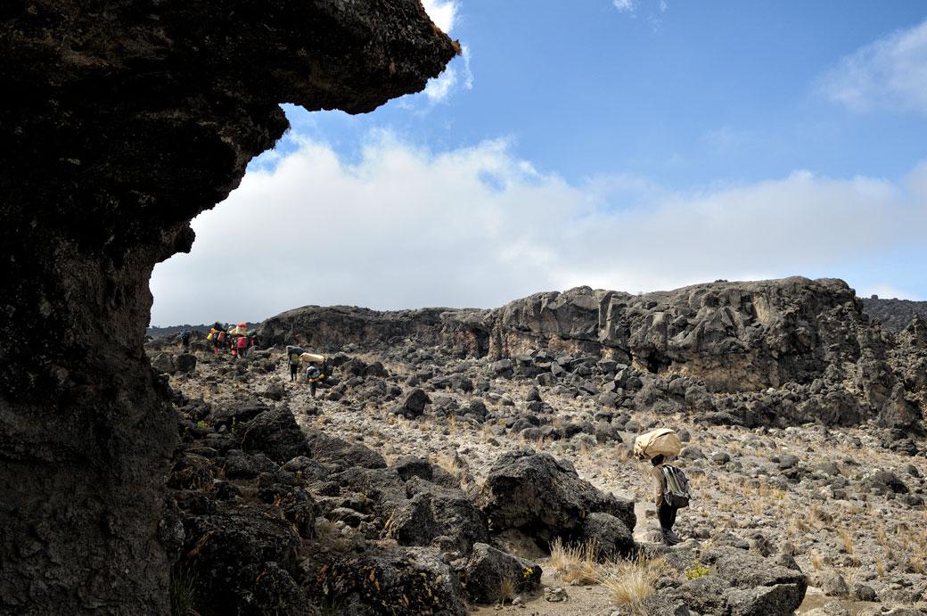 Porteurs dans un paysage volcanique sur le Kilimandjaro, Tanzanie