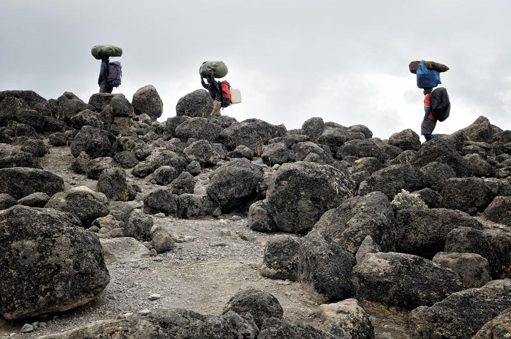Trois porteurs du Kilimandjaro et pierres volcaniques, Tanzanie