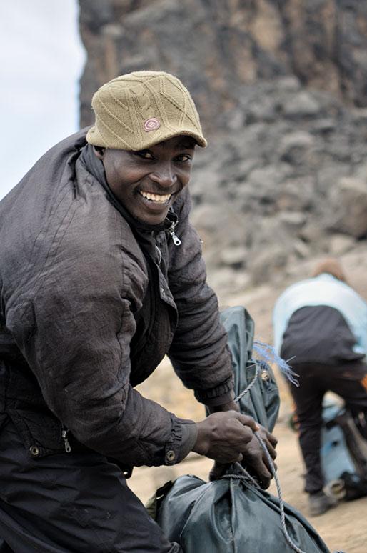 Porteur souriant au camp de Lava Tower qui prépare son sac, Tanzanie