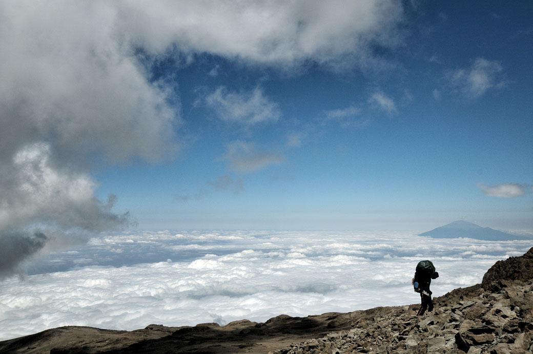 Porteur et nuages avec le mont Méru depuis le camp Barafu du Kilimandjaro