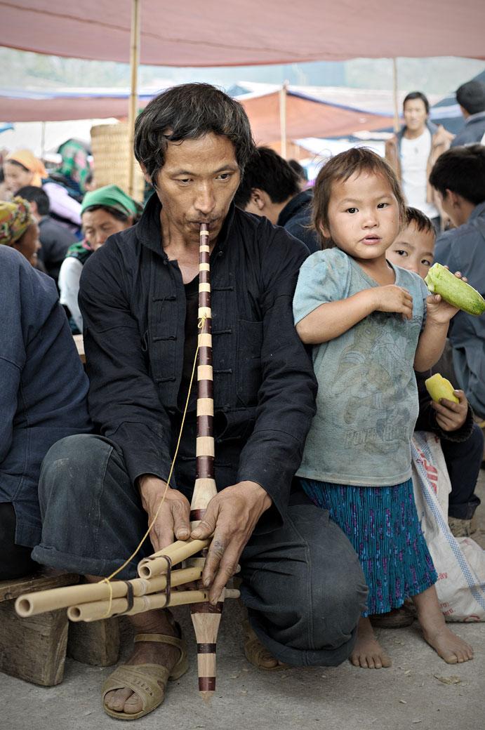 Homme qui joue d'un instrument de musique au marché de Meo Vac