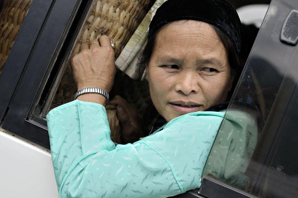 Femme qui regarde par la fenêtre d'un bus au marché de Meo Vac
