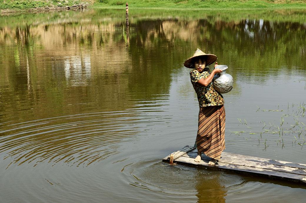 Jeune femme remplissant une jarre à eau à Mrauk U, Birmanie