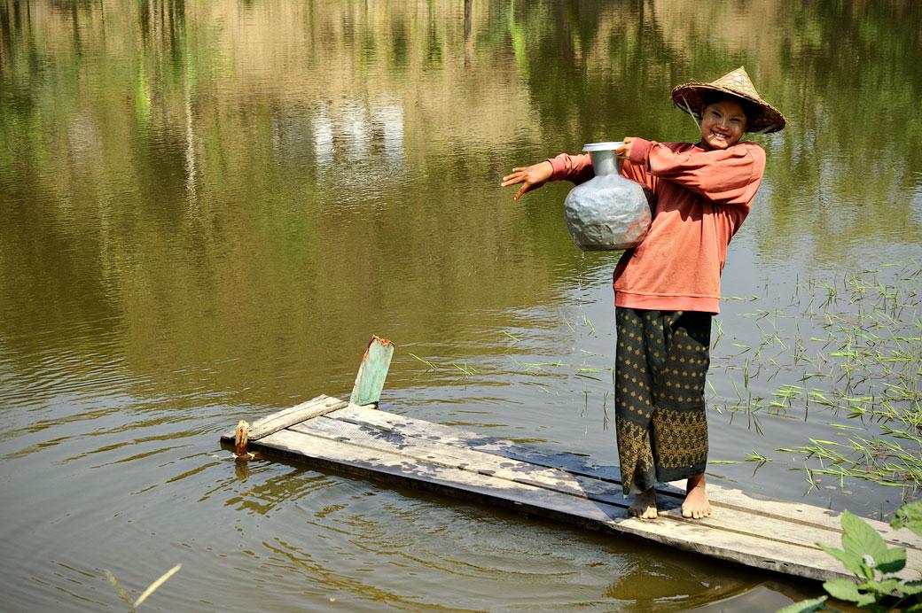 Jeune femme souriante avec une jarre à eau à Mrauk U
