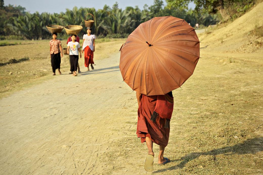 Moine et femmes marchant sur une route poussiéreuse à Mrauk U