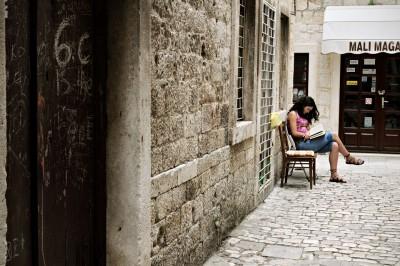 Jeune femme qui lit un livre à Trogir, Croatie