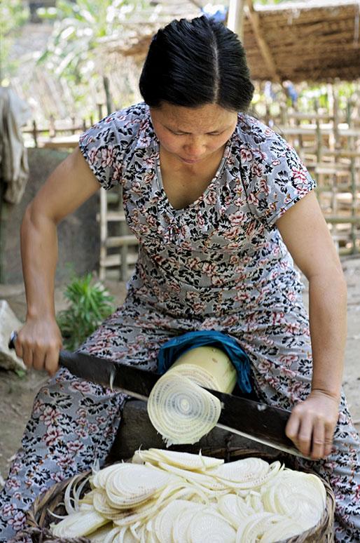 Femme qui découpe un tronc avec une machette, Vietnam