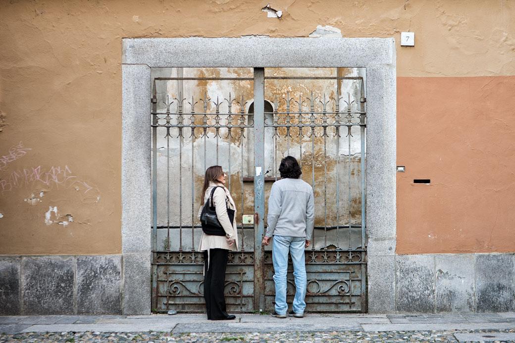Couple devant un portail de fer à Pavie, Italie