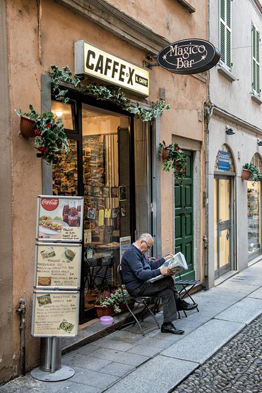 Homme qui lit son journal dans une rue de Pavie, Italie