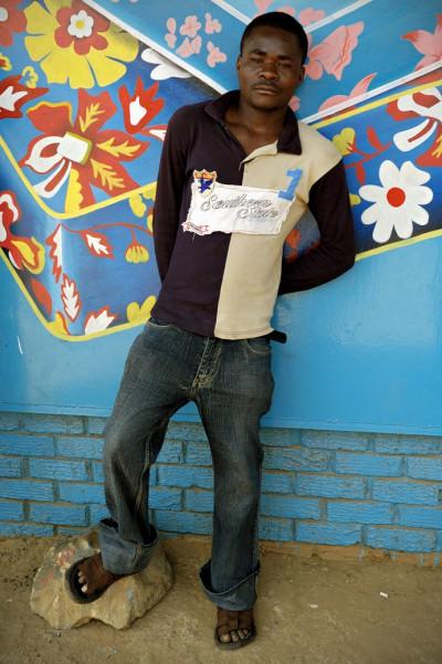Homme debout devant un mur bleu à Lusaka, Zambie
