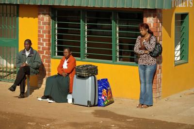 Trois personnes et des bagages à un arrêt de bus, Zambie