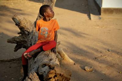 Jeune garçon assis sur un tronc d'arbre dans le village de Kawaza