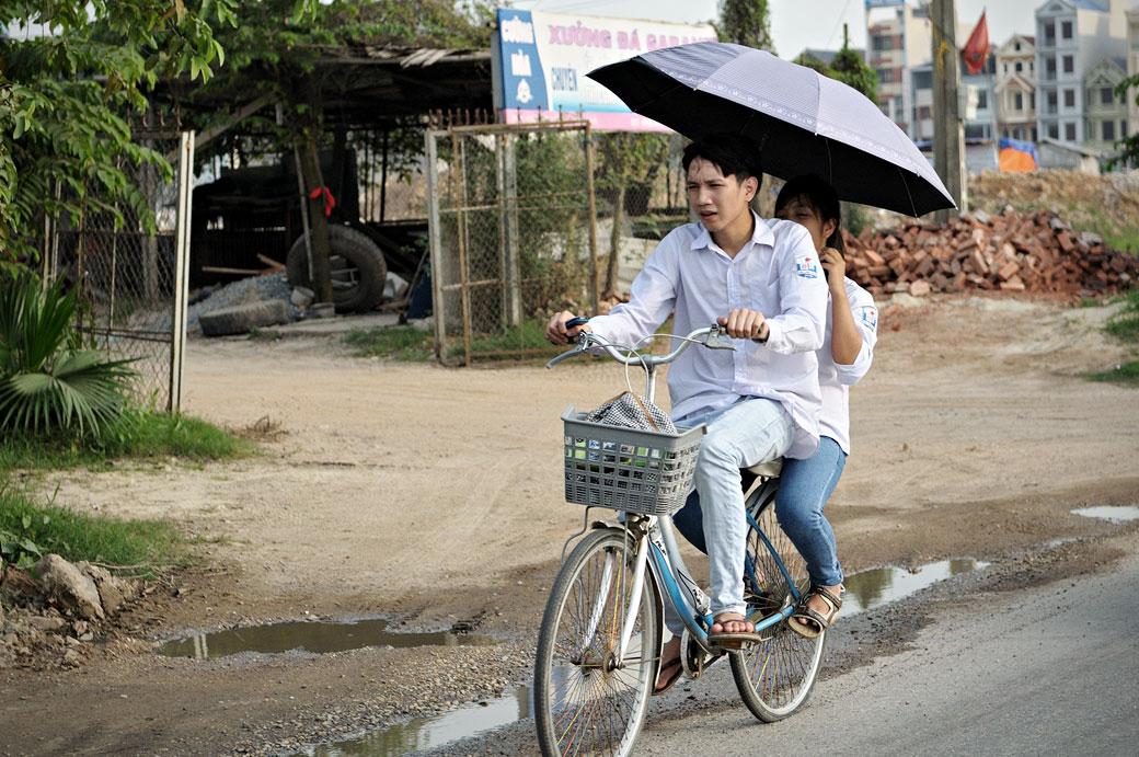 Deux étudiants sur un vélo avec une ombrelle, Vietnam