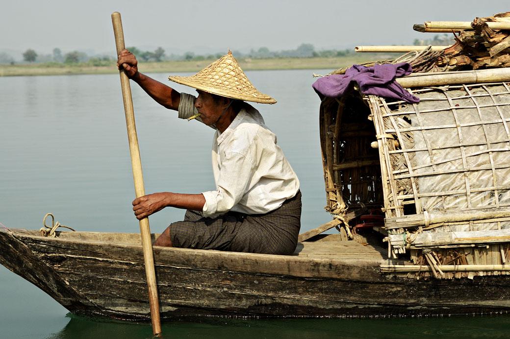 Homme qui fume en ramant sur la rivière Lemyo, Birmanie