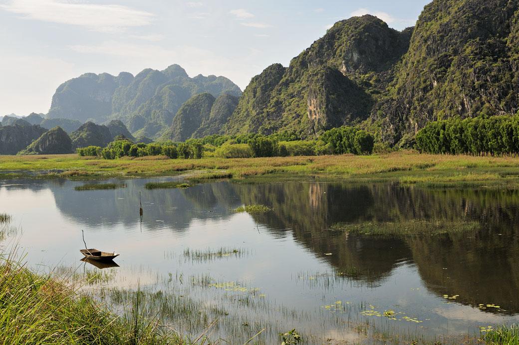 Barque et pics calcaires à Van Long, Vietnam