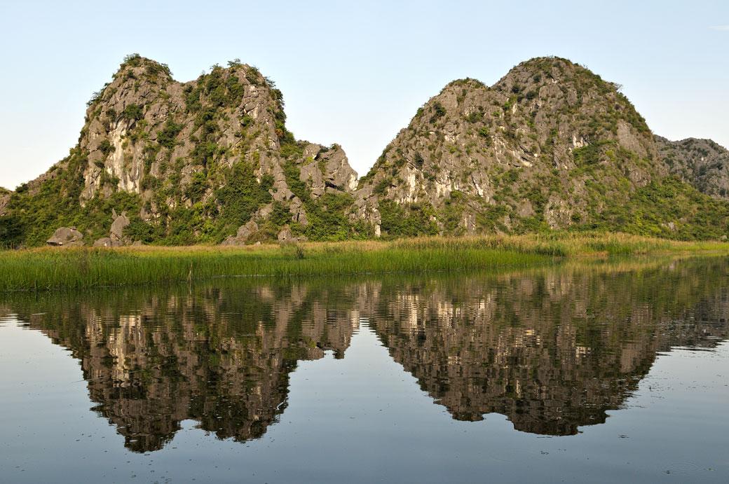 Réflexion de montagnes dans la réserve de Van Long, Vietnam