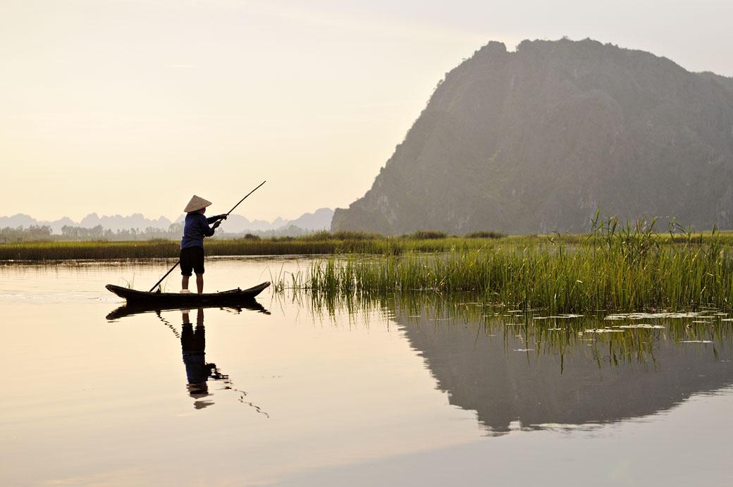 Femme debout sur une barque à la réserve de Van Long, Vietnam