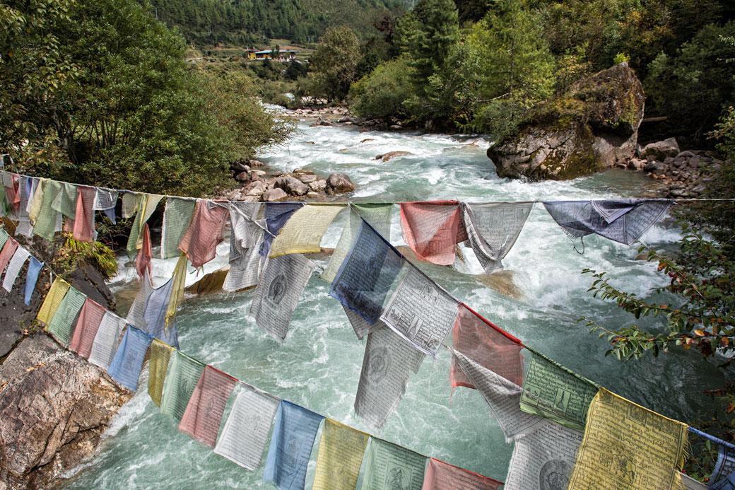 Drapeaux de prières au-dessus d'une rivière à Shana, Bhoutan