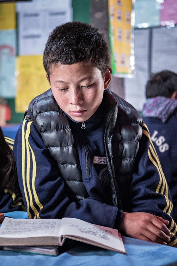 Garçon qui lit dans une classe d'école de Laya, Bhoutan
