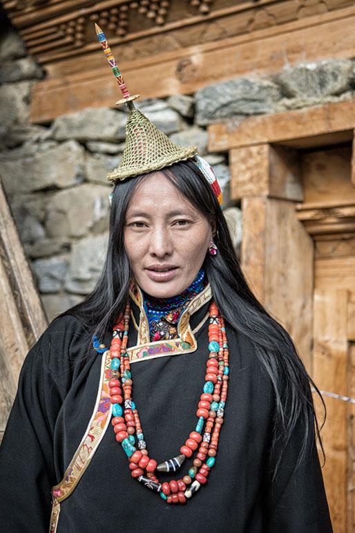 Femme Layap en tenue traditionnelle devant sa maison, Bhoutan