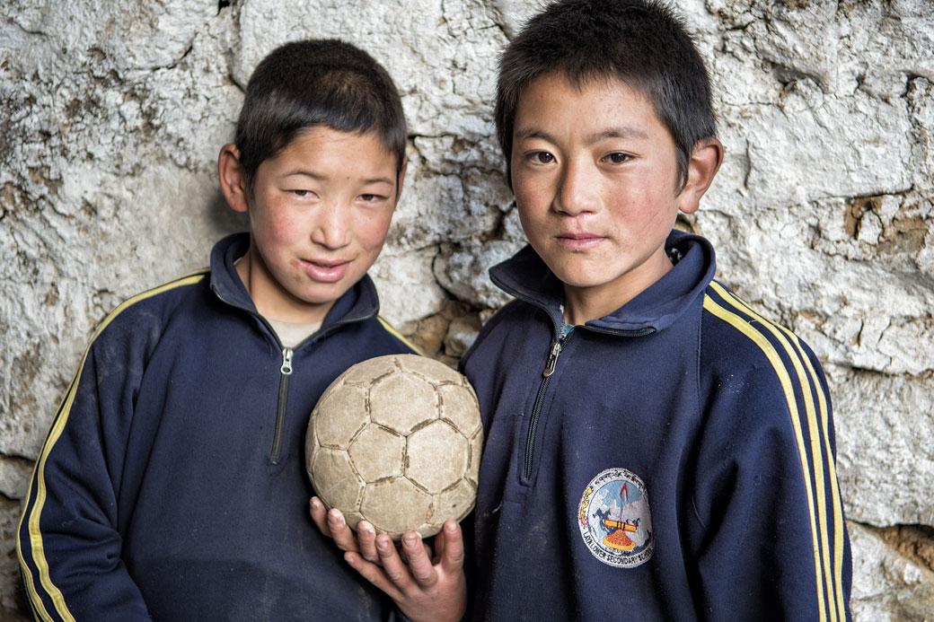 Deux écoliers avec leur ballon de foot à Laya, Bhoutan