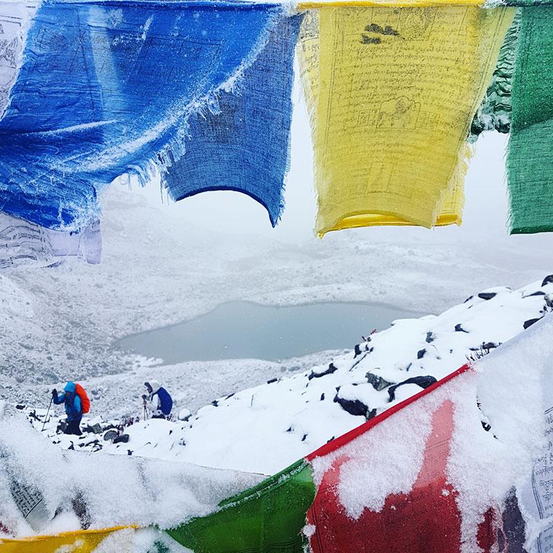 Trekkeurs et drapeaux de prières au col de Karakachu La, Bhoutan