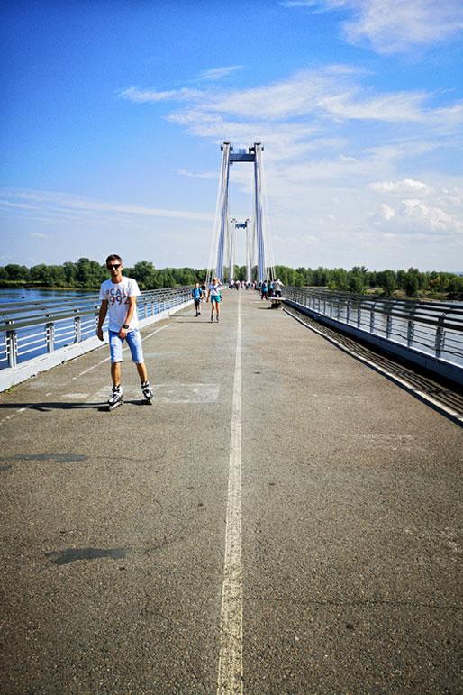 Homme en roller sur le pont Vinogradovsky à Krasnoyarsk, Russie