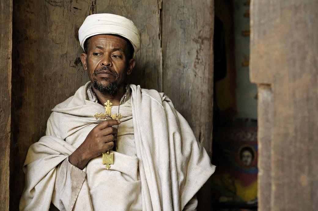 Prêtre tenant une croix devant la porte d'une église, Ethiopie