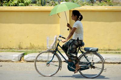 Jeune femme à vélo avec une ombrelle à Sittwe, Birmanie