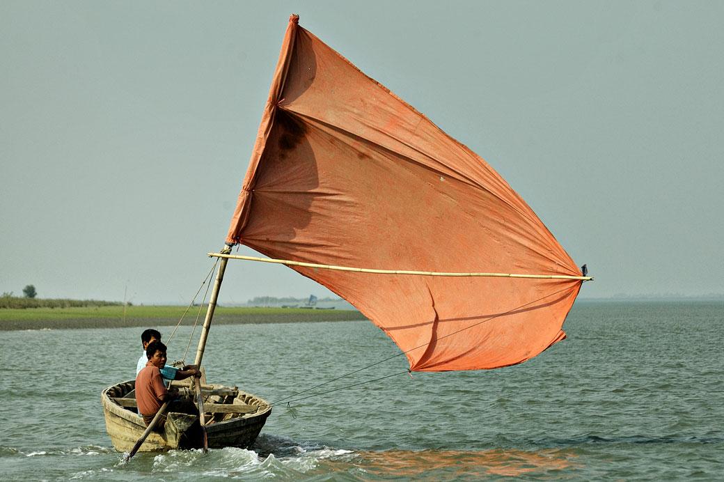 Bateau à voile orange sur le fleuve Kaladan à Sittwe, Birmanie