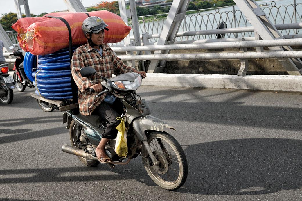 Moto chargée sur le pont Trang Tien à Hué, Vietnam