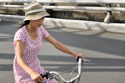 Femme à vélo sur le pont Trang Tien à Hué, Vietnam