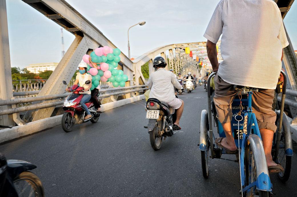Circulation de deux-roues sur le pont Trang Tien à Hué, Vietnam