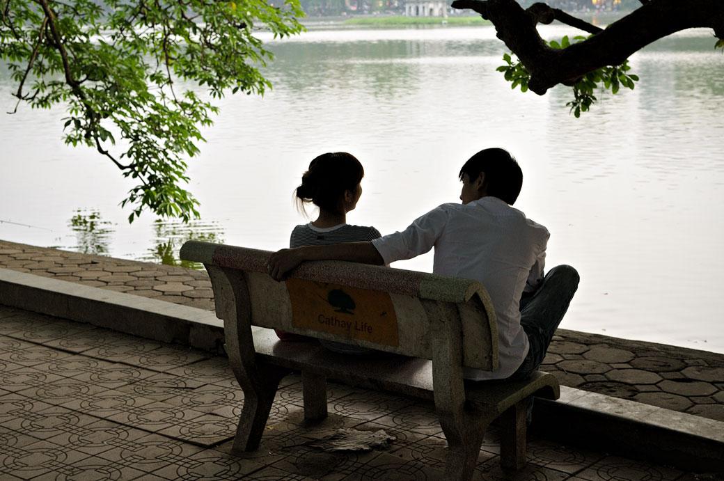 Jeune couple sur un banc au bord du lac Hoan Kiem à Hanoi, Vietnam