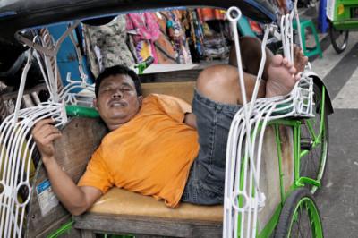 Homme qui fait la sieste dans son cyclo-pousse à Yogyakarta, Indonésie
