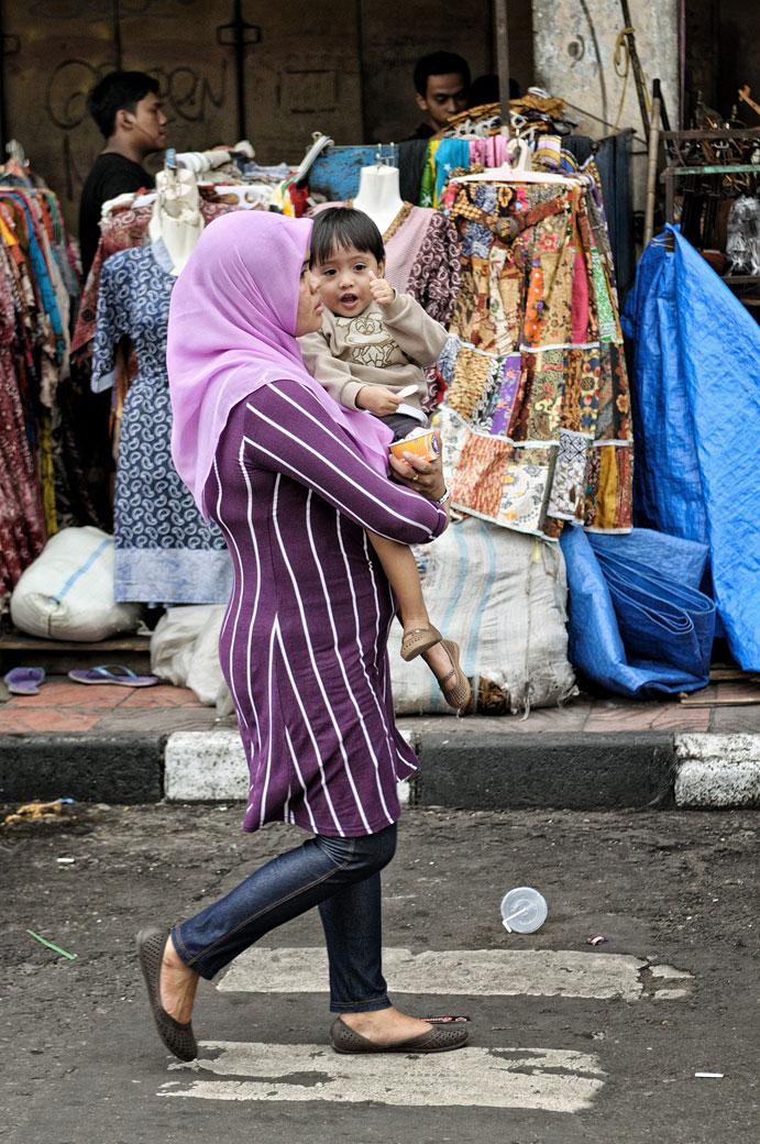 Femme voilée portant son enfant dans une rue de Yogyakarta, Indonésie