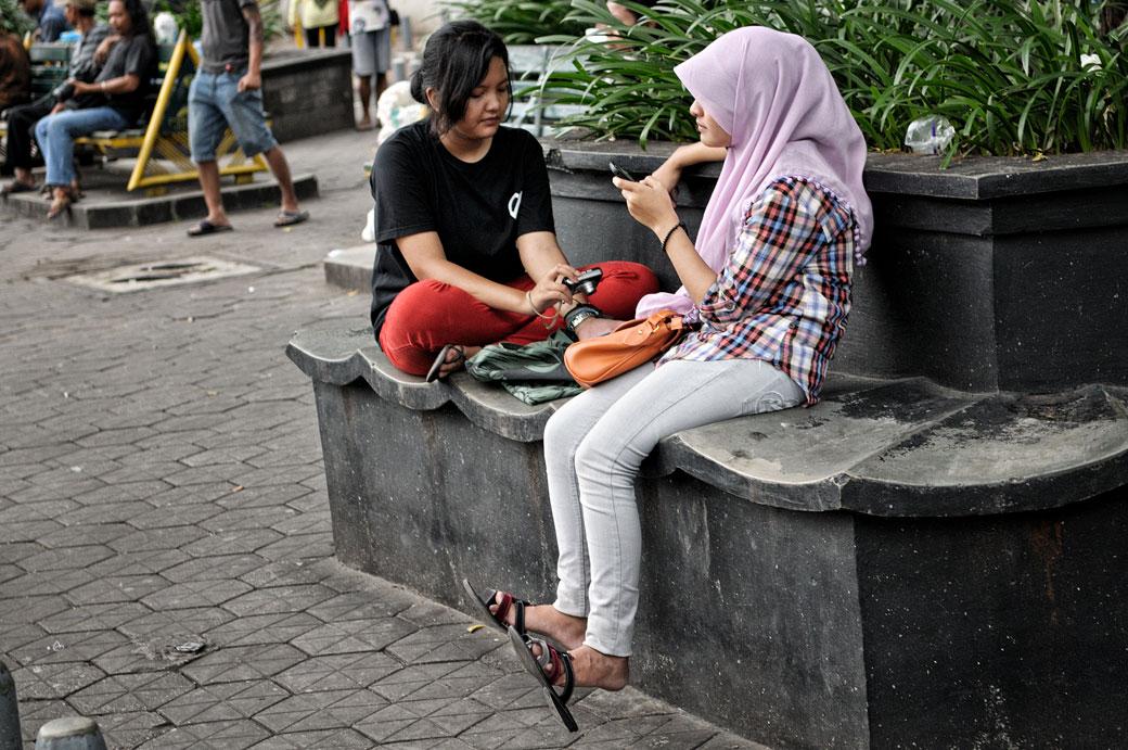 Jeunes femmes sur un banc à Yogyakarta, Indonésie
