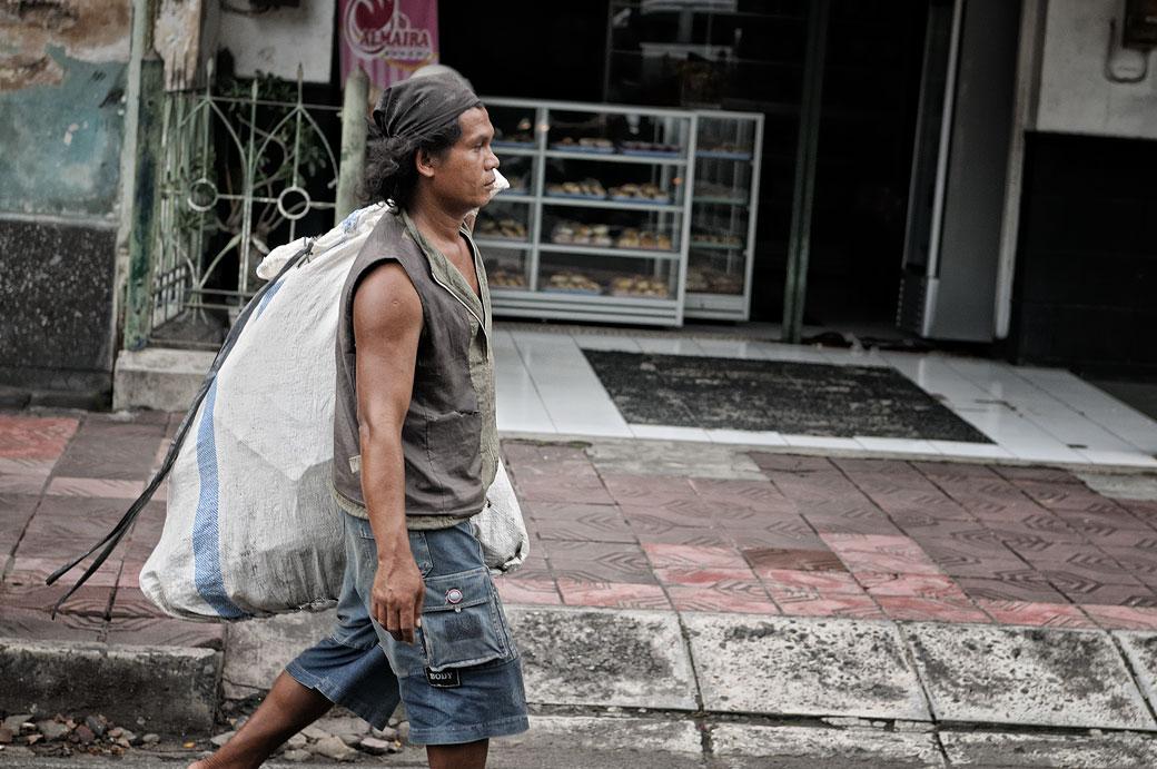 Homme avec un gros sac à Yogyakarta, Indonésie