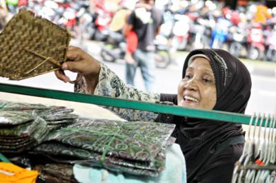 Femme qui dépoussière son shop à Yogyakarta, Indonésie