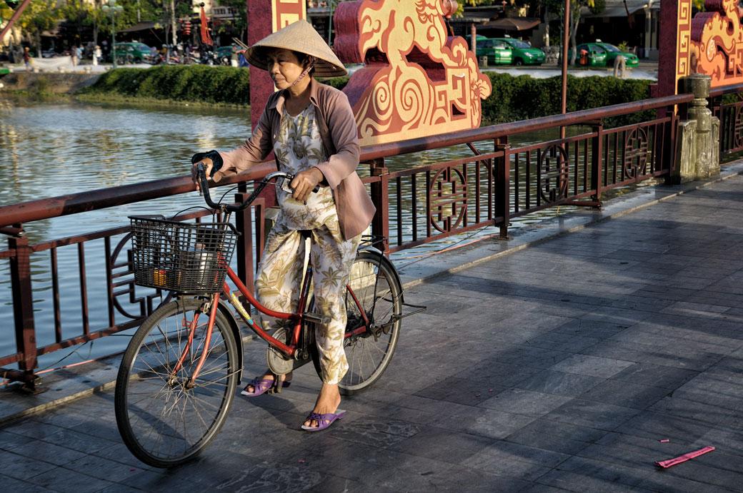 Femme à vélo sur un pont de Hoi An, Vietnam