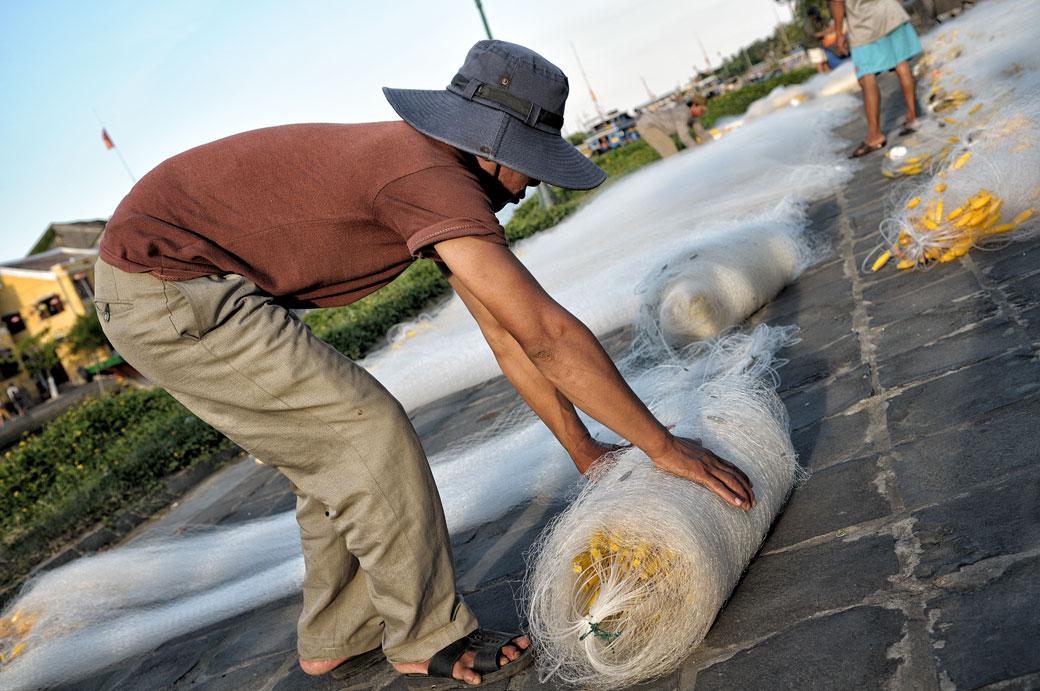 Homme qui enroule ses filets de pêche à Hoi An, Vietnam