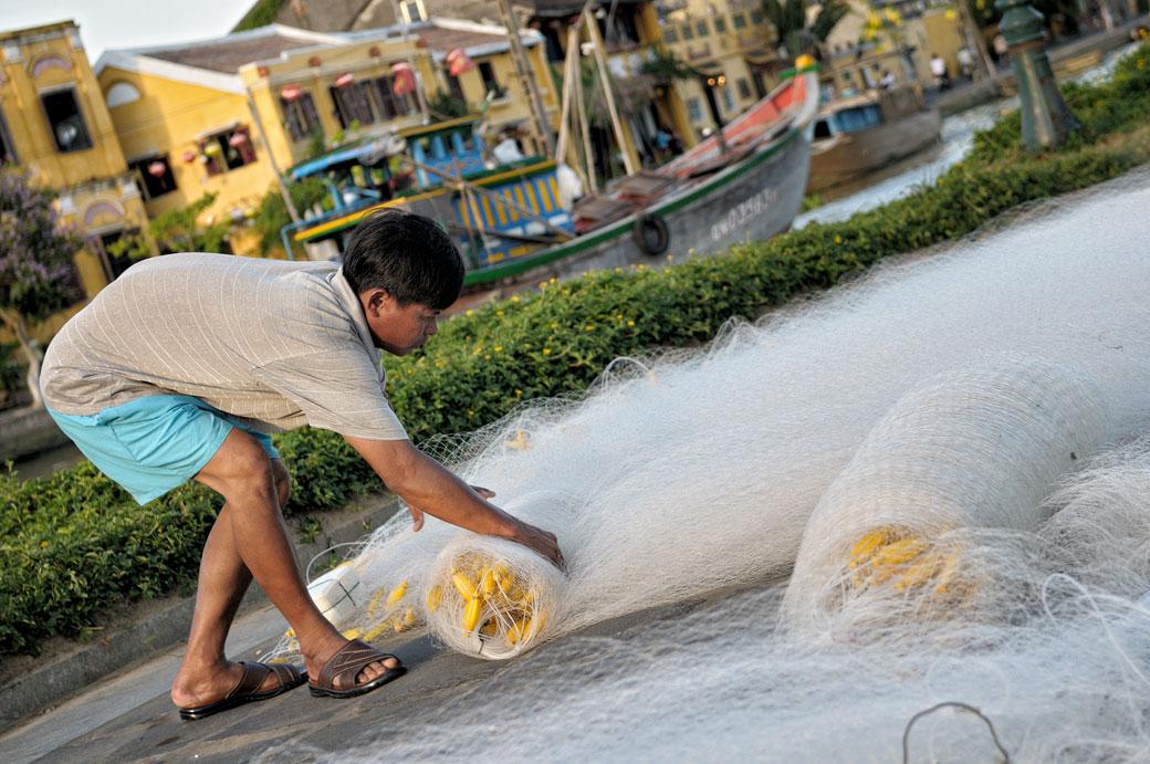 Homme enroulant des filets de pêche à Hoi An, Vietnam