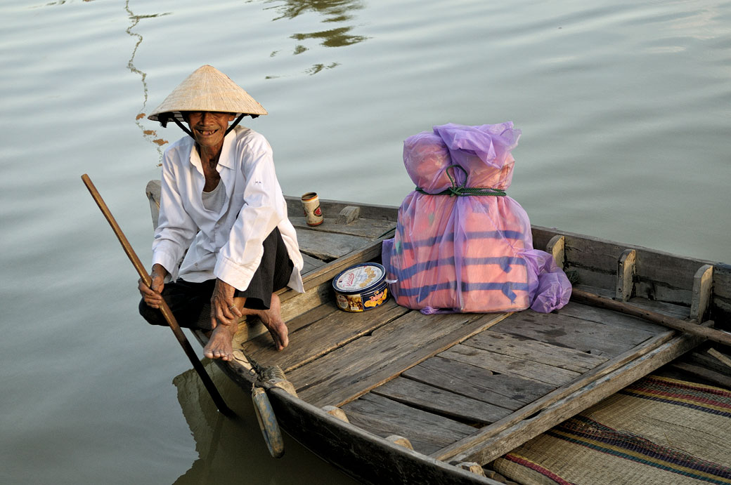Vieil homme heureux sur une barque à Hoi An, Vietnam