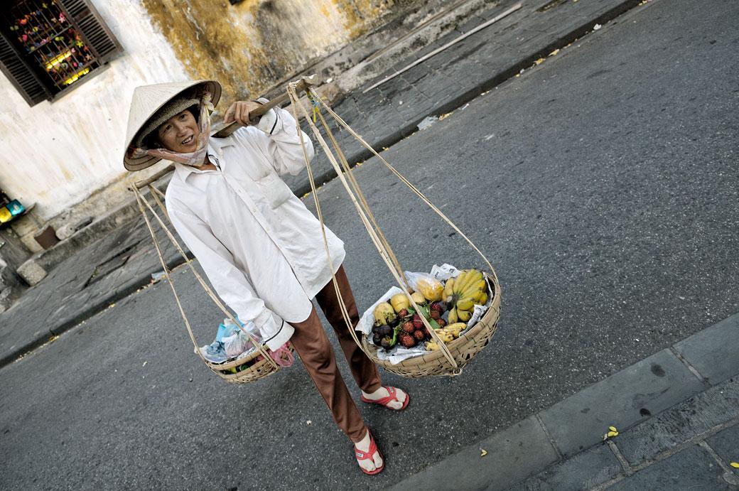Femme avec des paniers de fruits à Hoi An, Vietnam