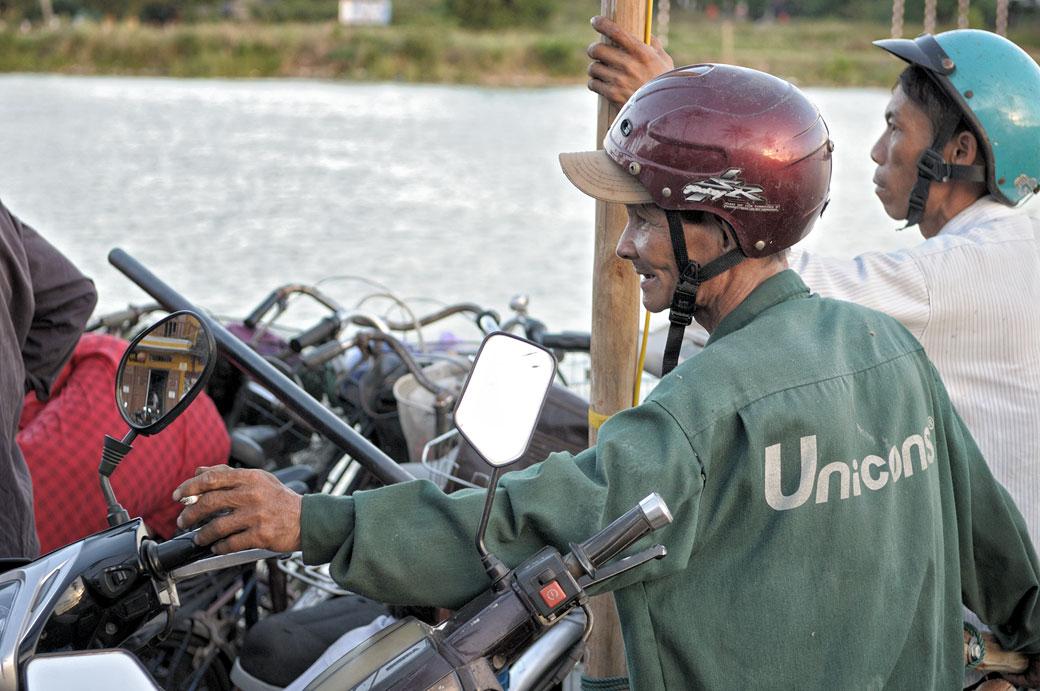 Hommes casqués sur un ferry à Hoi An, Vietnam