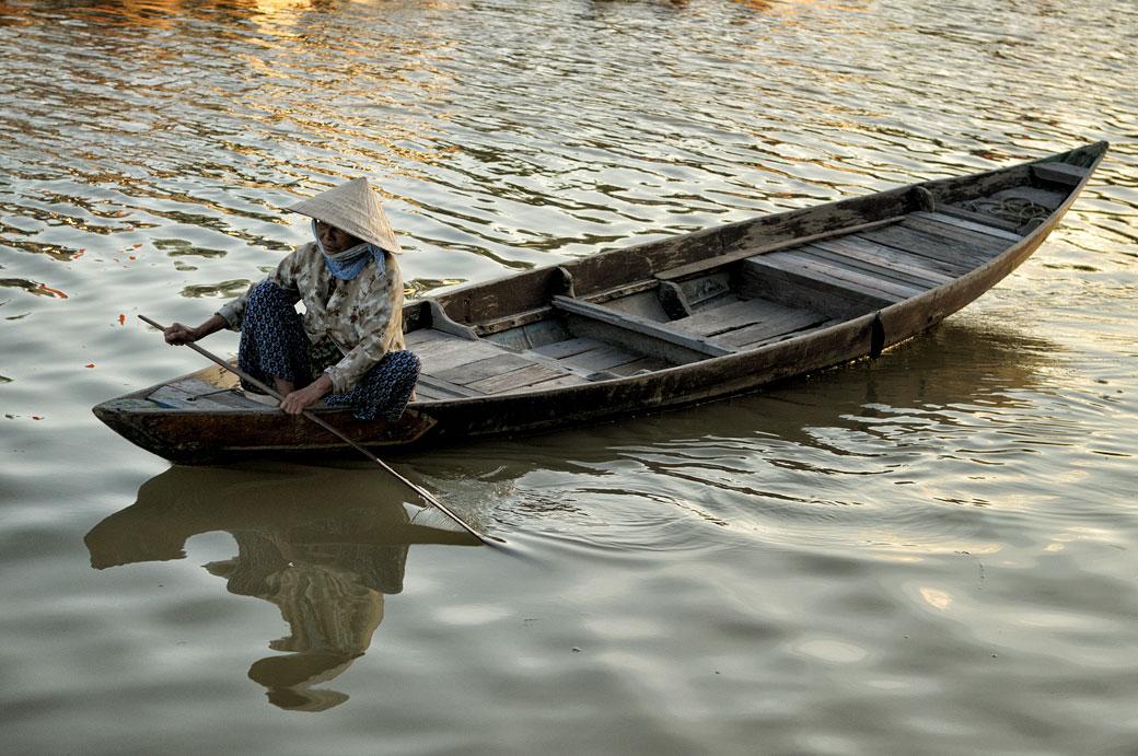 Femme sur une barque en bois à Hoi An, Vietnam